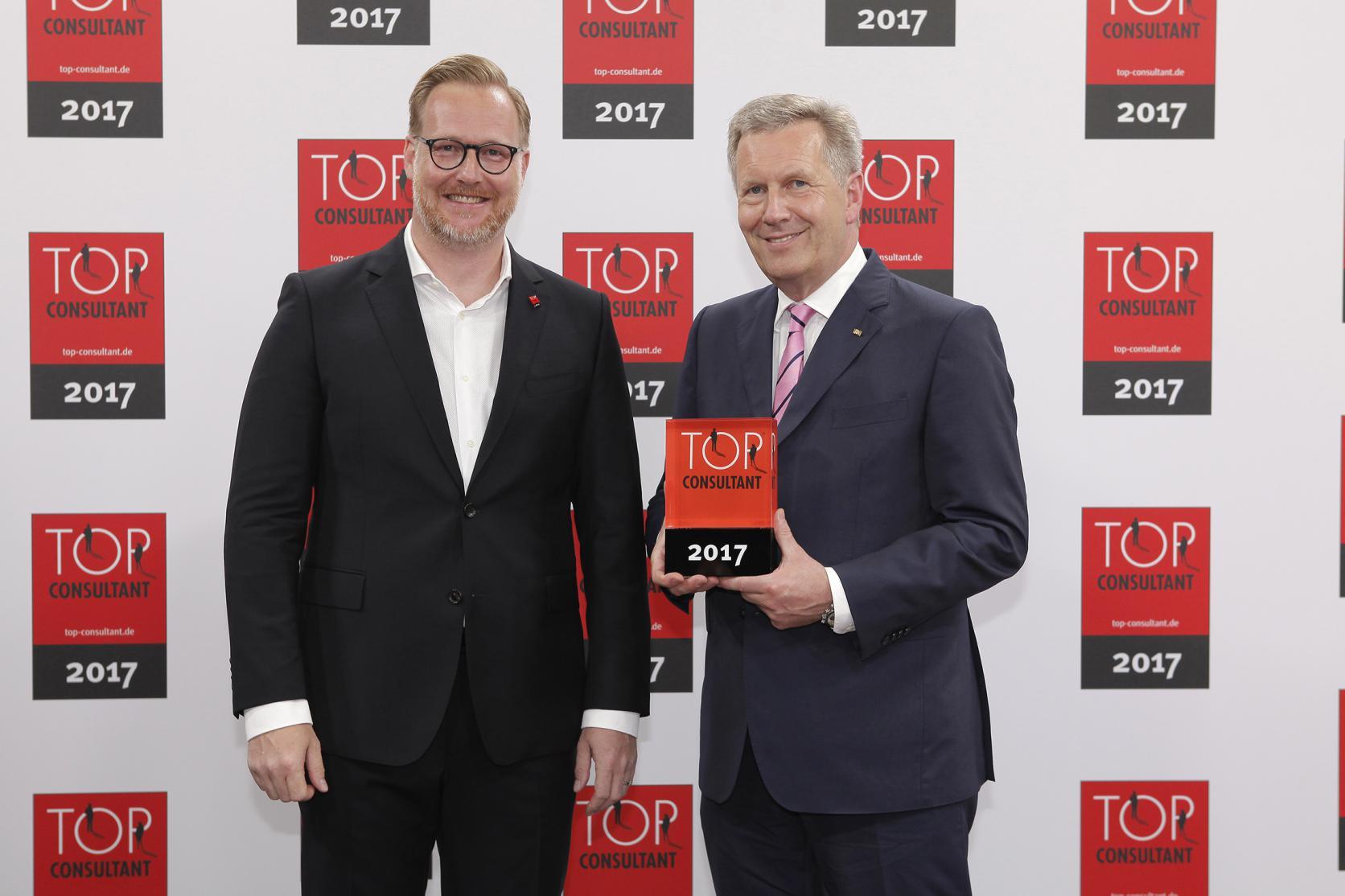 Oliver Hendy, Direktor bei Atreus, nimmt die Auszeichnung TOP Consultant 2017 von Christian Wulff entgegen